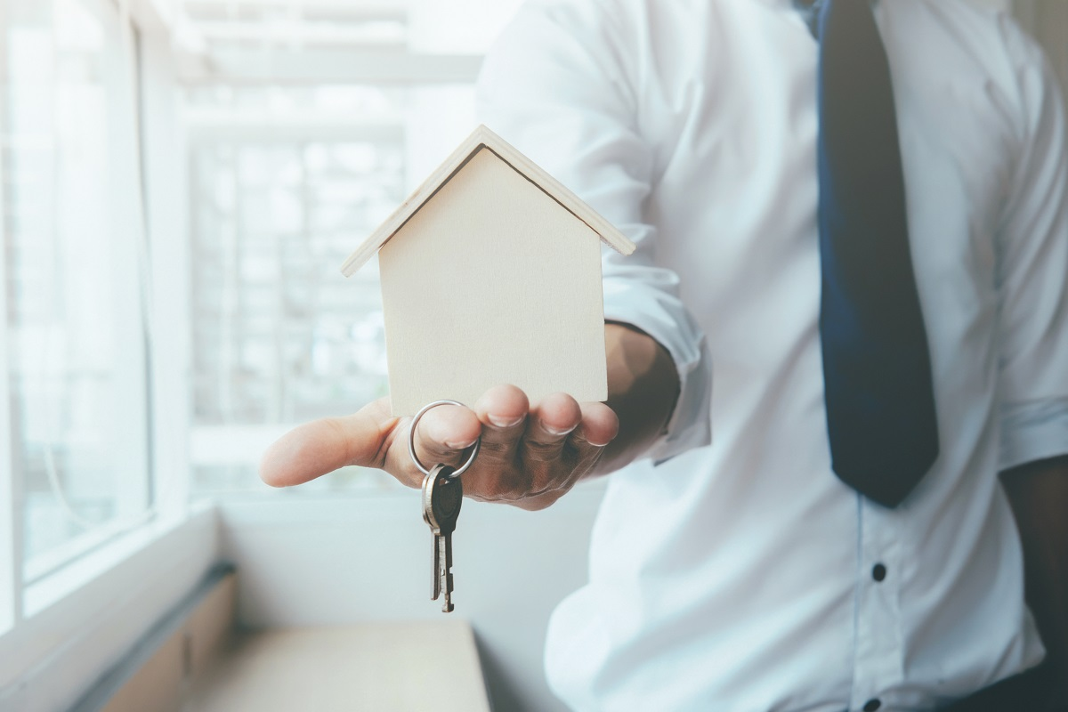 Real Estate Education in NY Salesperson holding keys to house